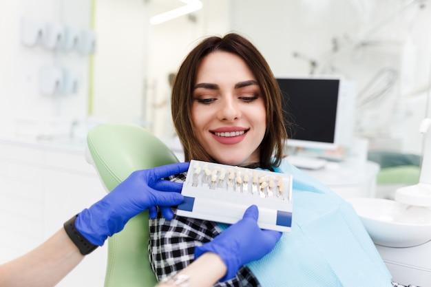Le dentiste et son patient choisissent un ton de placage. docteur en dentisterie montre une palette avec des nuances pour les dents