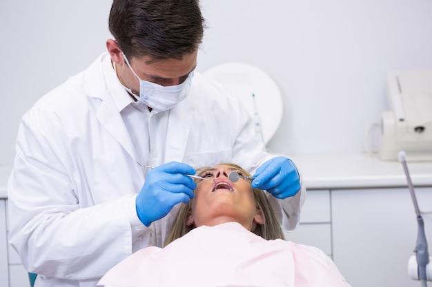Dentiste tenant l'équipement tout en nettoyant les dents de la femme