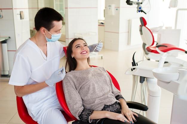 Le dentiste traite les dents avec une belle femme