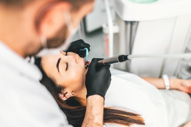 Dentiste travaillant dans une clinique dentaire avec une patiente dans son fauteuil