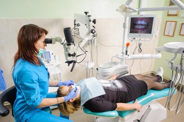 Dentiste travaillant avec un microscope à la clinique de dentiste moderne