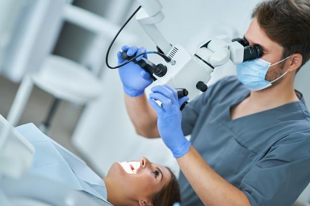 Dentiste vérifiant les dents du patient avec un microscope au bureau de chirurgie