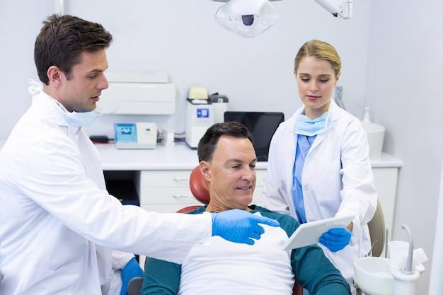 Dentistes montrant le rapport dentaire sur tablette numérique