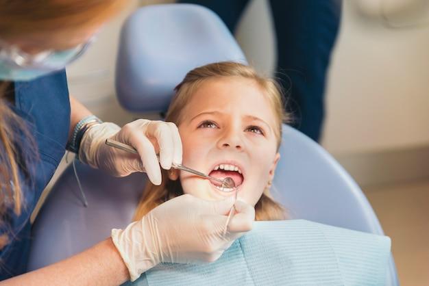 Dentistes avec un patient lors d'une intervention dentaire chez une fille. concept de dentiste