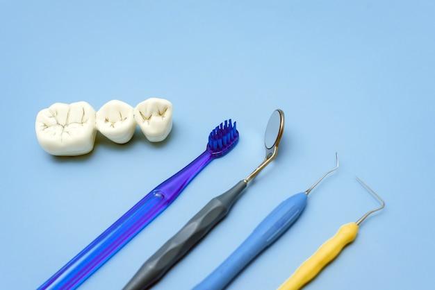Dents artificielles avec caries et brosse à dents avec outils dentaires