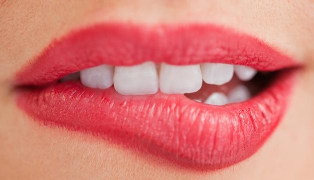 Dents blanches d'une femme se mordant les lèvres