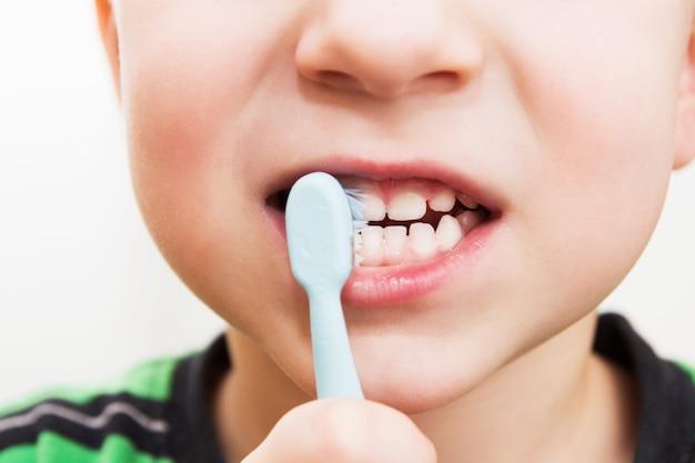 Les dents de l'enfant avec une brosse à dents