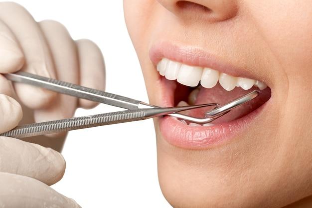 Dents de femme et un miroir de bouche de dentiste sur le fond