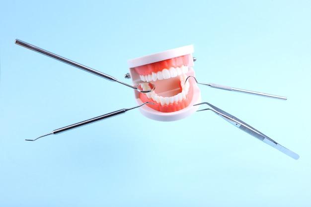 Les dents modèles et les instruments dentaires lévitent dans les airs sur fond bleu