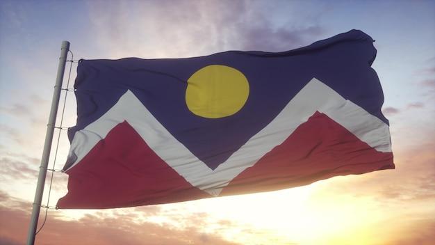 Denver ville du colorado drapeaux dans le vent, le ciel et le soleil. rendu 3d