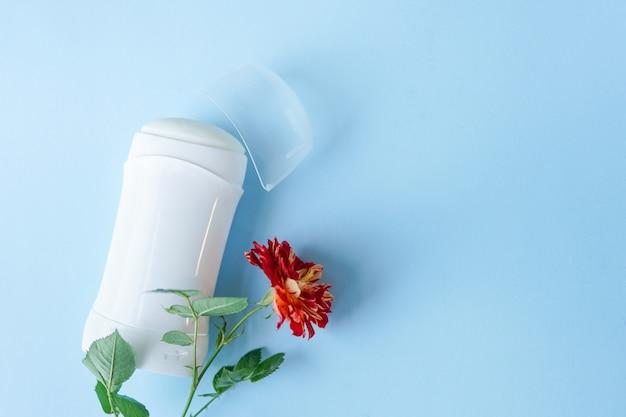 Déodorant antisudorifique pour le corps avec fleur sur bleu, espace copie, modèle