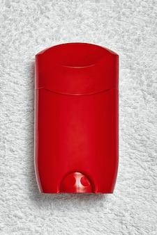 Déodorant bâton de déo rouge sur une serviette blanche, vue du dessus