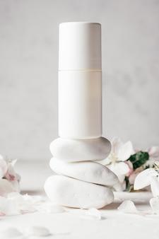 Déodorant à bille anti-transpirant sur une pile de cailloux blancs, sur une surface en plâtre clair avec des fleurs de pomme