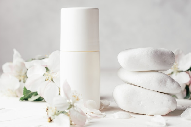 Déodorant à bille anti-transpirant près d'une pile de cailloux blancs sur une surface en plâtre clair, avec des fleurs de pomme