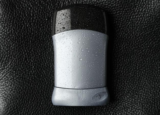 Déodorant corporel sur fond noir, espace vide pour le texte