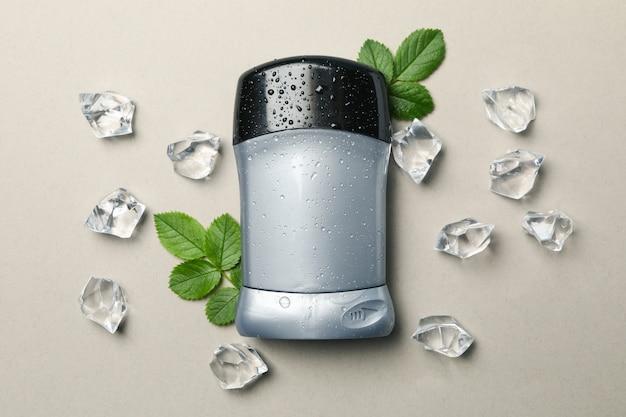 Déodorant corporel, glace et feuilles sur fond gris, espace vide pour le texte