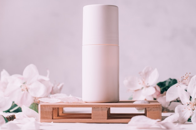Déodorant roll-on anti-transpirant sur podium en bois en forme de palette, sur surface en plâtre clair avec fleurs de pomme
