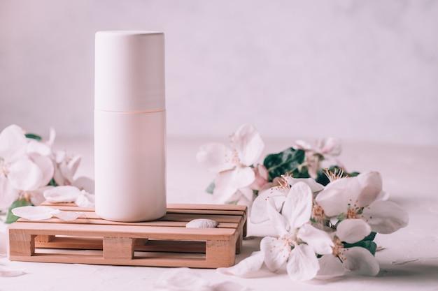 Déodorant roll-on anti-transpirant sur podium en bois sous forme de palette sur une surface en plâtre clair avec des fleurs de pomme. espace de copie