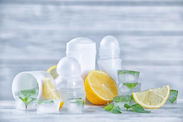 Déodorants pour femmes, citrons et menthe sur table