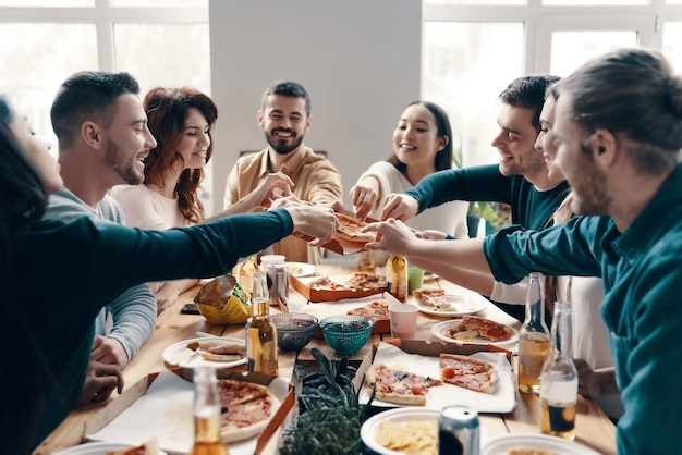 Dépêchez-vous de choisir la meilleure tranche! groupe de jeunes en tenue décontractée cueillant une pizza et souriant tout en dînant à l'intérieur