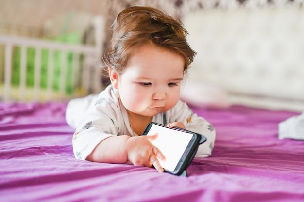La dépendance des enfants aux téléphones. rayonnement du téléphone à l'enfant. un petit garçon de 0 à 1 ans avec un smartphone dans les mains regarde l'écran avec enthousiasme. dépendance aux gadgets pour enfants