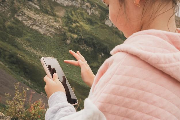 Dépendance des enfants à l'égard des gadgets et des jeux, la fille joue à des jeux sur son smartphone éducation numérique i ...