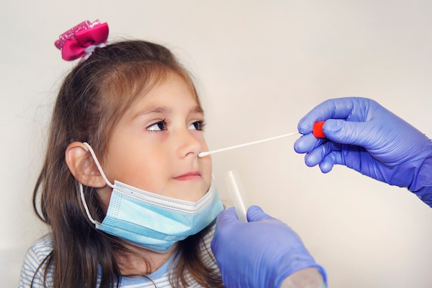 Dépistage du virus, médecin prélevant un échantillon de test de mucus nasal du nez effectuant une procédure de test de virus respiratoire. contrôle des fosses nasales en orl. fille dans un masque protecteur au rendez-vous chez le médecin.