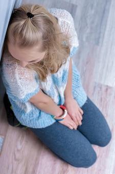 Dépression femme blonde s'asseoir sur la vue de dessus du sol