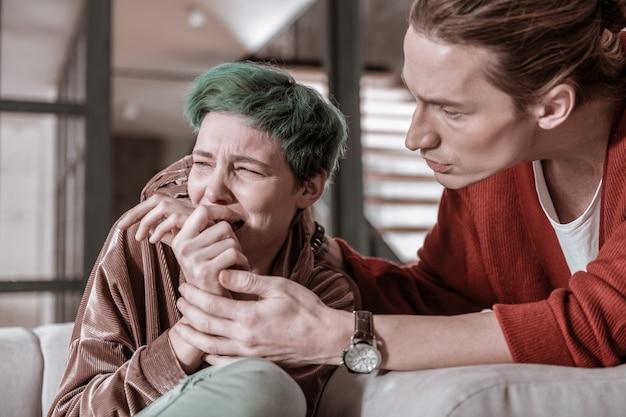 Dépression nerveuse. femme aux cheveux verts ayant une dépression nerveuse après une bagarre avec son petit ami