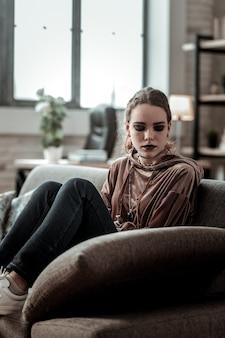 Déprimé après l'école. adolescent émotionnel élégant assis sur un canapé se sentant très déprimé après l'école