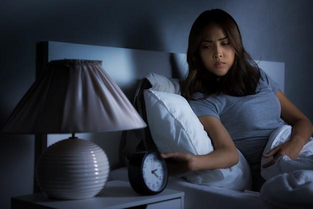 Déprimé jeune femme asiatique assise dans son lit ne peut pas dormir d'insomnie