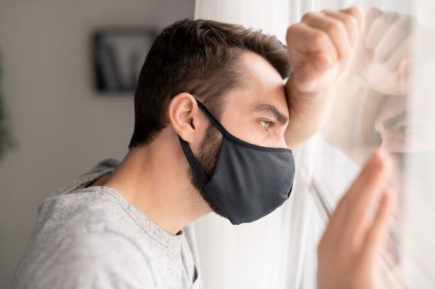 Déprimé jeune homme en masque de tissu appuyé sur la fenêtre tout en rêvant de la vie sociale