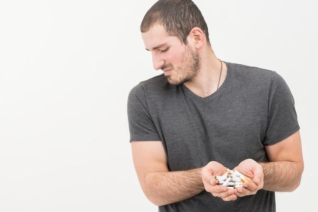 Déprimé jeune homme tenant des cigarettes cassées à la main isolé sur fond blanc