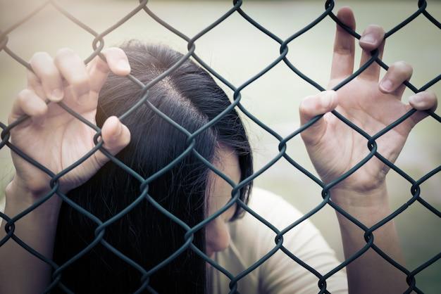Déprimé, problème et solution. des femmes désespérées passent la main sur une clôture grillagée.