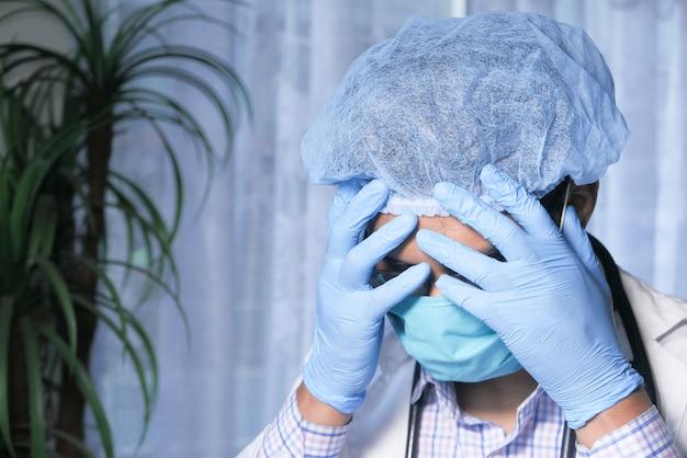 Déprimé triste médecin mûri couvrant le visage avec les mains