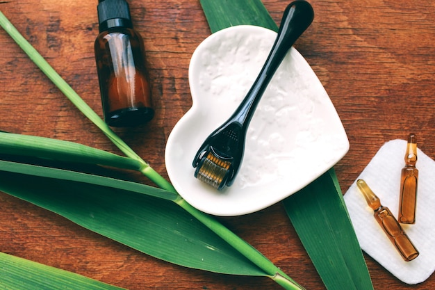 Dermaroller et sérum à côté d'une crème anti-âge pour le visage industrie de la beauté close-up dermaroller pour la thérapie des micro-aiguillages médicaux