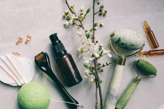 Dermaroller et sérum à côté d'une crème anti-âge pour le visage industrie de la beauté dermaroller pour la thérapie par micro-aiguilletage médical derma roller mesoroller pour la mésothérapie près des fleurs