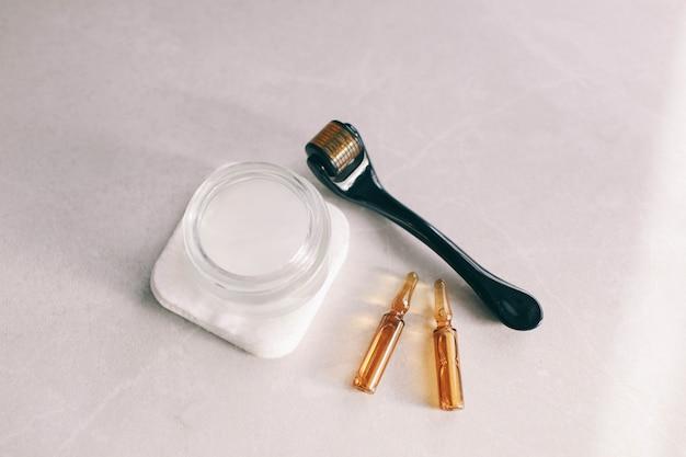 Dermaroller et sérum à côté d'une crème anti-âge pour le visage