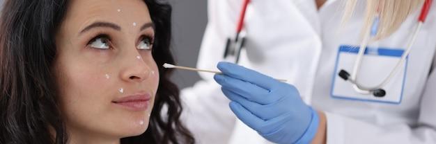 Un dermatologue applique une crème blanche aux patients confrontés au concept de visage de procédures anti-âge