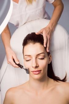 Dermatologue effectuant une épilation au laser sur un patient