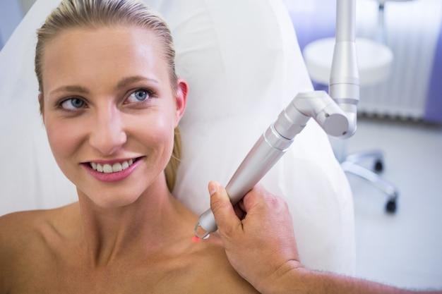Dermatologue enlevant la taupe de l'épaule de la femme