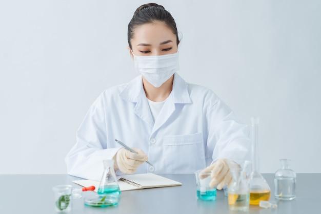 Dermatologue Féminin Faisant Des Recherches Pour Un Nouveau Produit De Soin De La Peau à Table, Gros Plan Photo Premium