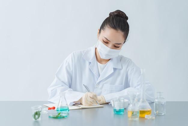 Dermatologue féminin faisant des recherches pour un nouveau produit de soin de la peau à table, gros plan