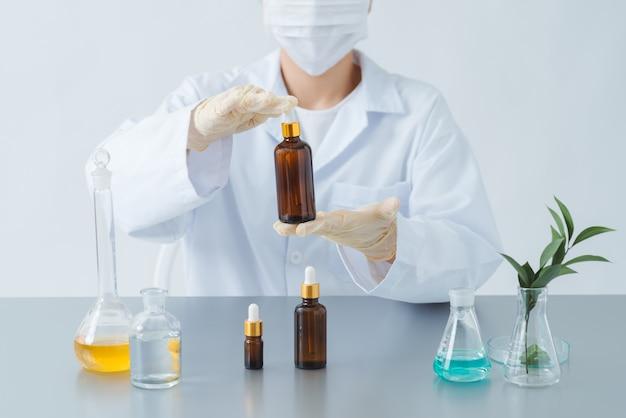 Dermatologue féminin tenant une bouteille de produit de soin de la peau sur la table, gros plan