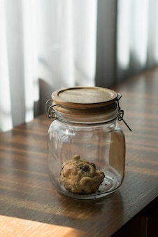 Le dernier cookie dans le bocal en verre laissé sur la table.