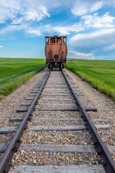 Le dernier wagon d'une longue file avec une voie au premier plan dans une région rurale de la saskatchewan, au canada