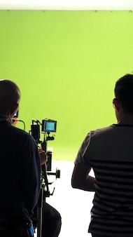 Derrière la caméra vdo dans la production en studio qui tire ou filme un fond d'écran vert