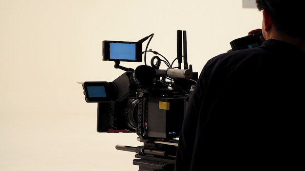 Derrière l'équipe de production de tournage vidéo travaillant et un ensemble d'équipements de caméra full hd en studio