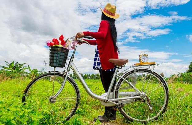 De derrière, une femme porte un chapeau marron et se tient près du vélo vintage