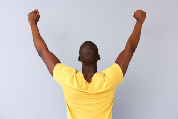 Derrière un homme noir joyeux avec les bras levés